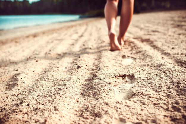 Huellas en la arena con patas de niña andante. Foto Premium