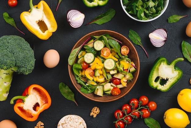 Huevo entero entero y ensalada mixta de vegetales frescos en mostrador negro Foto gratis