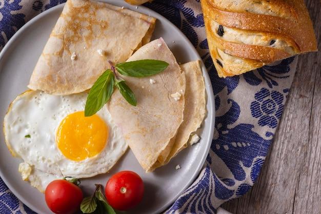 Huevo frito con crepes y tomates Foto gratis