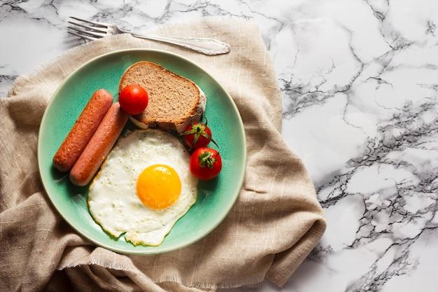 Huevo frito con perritos calientes y tomates Foto gratis