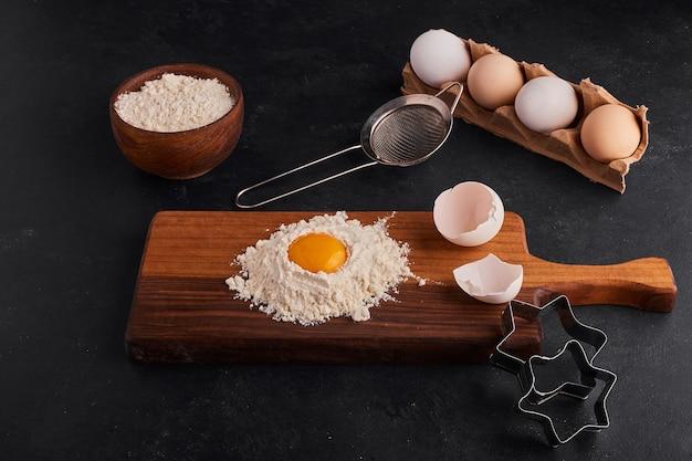 Huevo y harina mezclados entre sí sobre tabla de madera con forma de galleta alrededor. Foto gratis