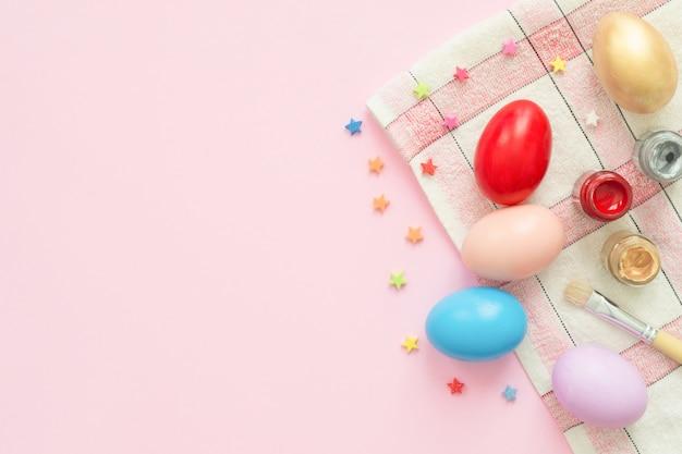 Huevo de pascua colorido pintado en composición de colores pastel con pincel Foto gratis