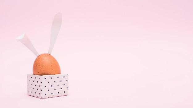 Huevo de pascua con orejas de conejo en caja Foto gratis