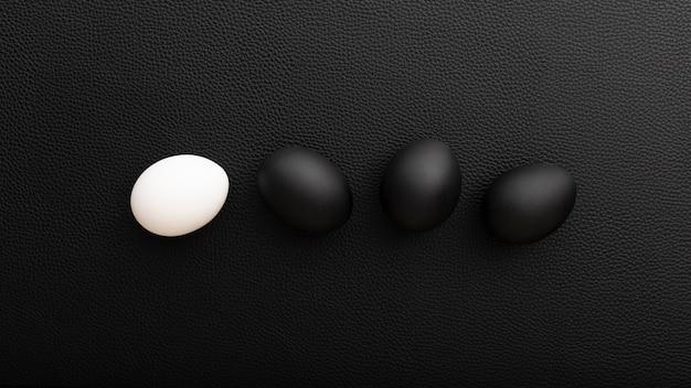 Huevos blancos y negros sobre una mesa oscura Foto gratis