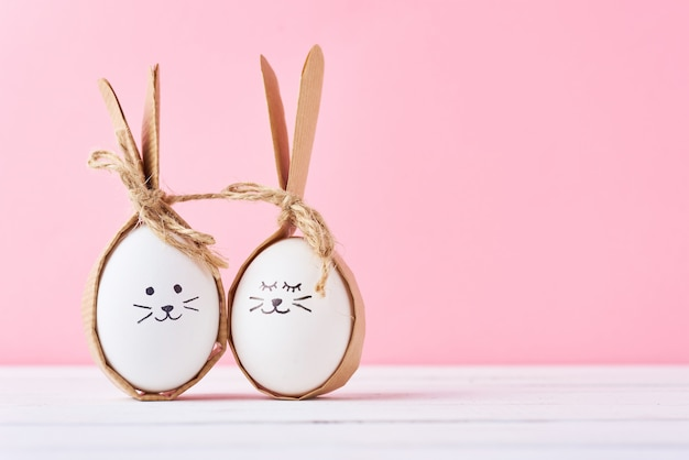 Huevos caseros divertidos con las caras en un fondo rosado. pascua o feliz pareja concepto Foto Premium
