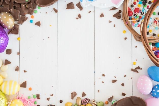 Huevos de chocolate de pascua con caramelos en mesa de madera Foto gratis