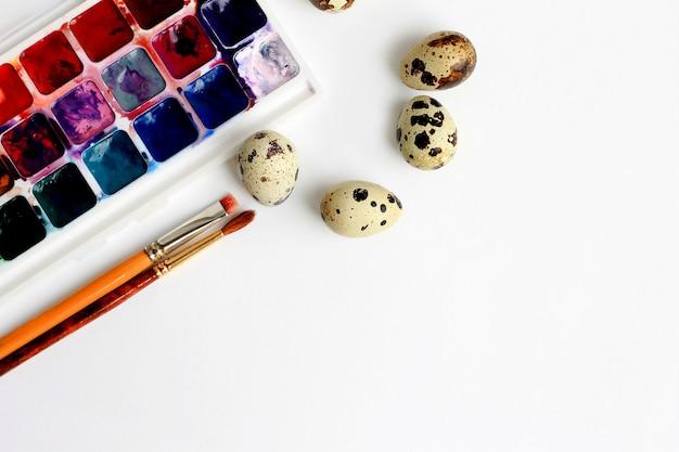 Huevos de codorniz, pinturas de acuarela y pinceles sobre un fondo azul Foto Premium