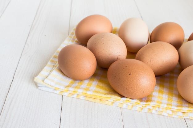 Huevos frescos en paquete de cartón en madera blanca Foto gratis