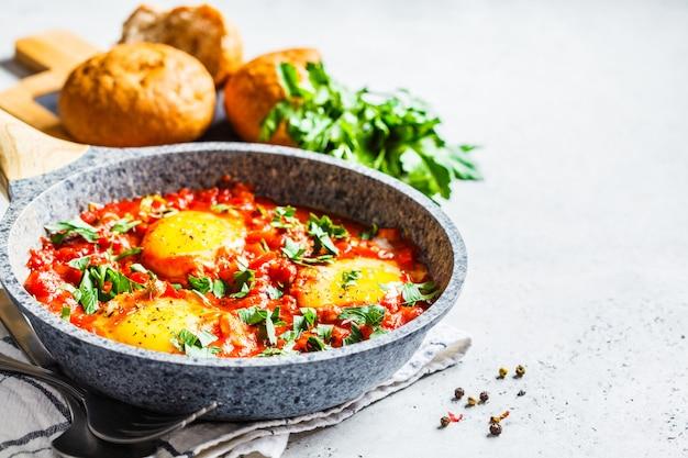 Huevos fritos en salsa de tomate con hierbas. Foto Premium