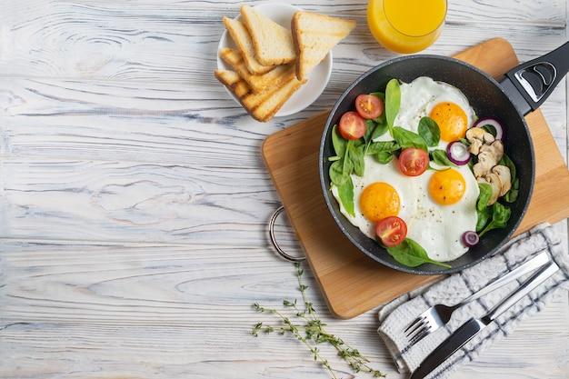 Huevos fritos con tomate, champiñones y hojas de espinaca en sartén Foto Premium