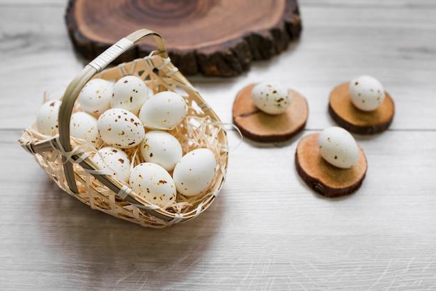 Huevos de gallina blanca en canasta sobre mesa Foto gratis
