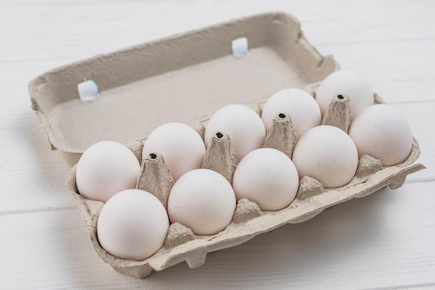 Huevos de gallina blanca en parrilla en mesa de luz Foto gratis