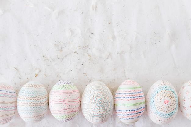 Huevos de gallina con estampados cerca de las plumas sobre textil Foto gratis