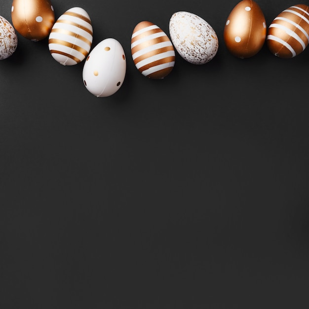Huevos de oro sobre fondo negro Foto gratis
