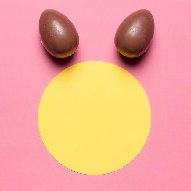 Huevos de pascua como oreja de conejo sobre el marco en blanco de papel redondo con fondo rosa Foto gratis