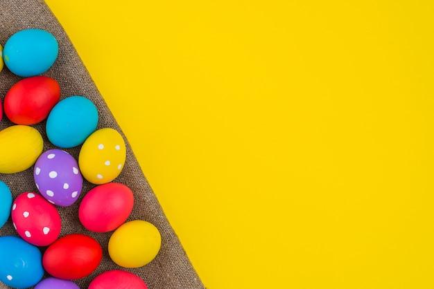 Huevos de pascua esparcidos sobre lienzo sobre mesa Foto gratis