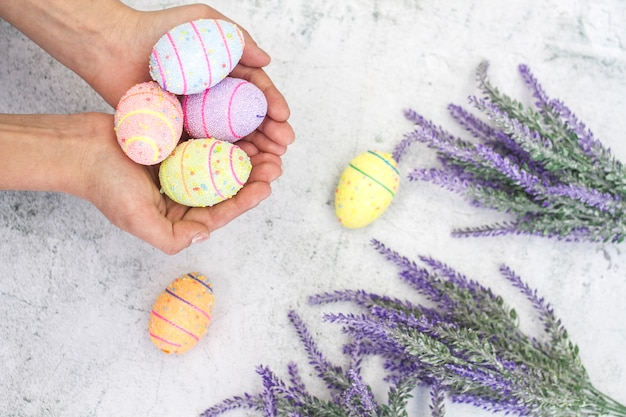 Huevos de pascua multicolores en manos femeninas sobre un fondo de primer plano de flores Foto Premium