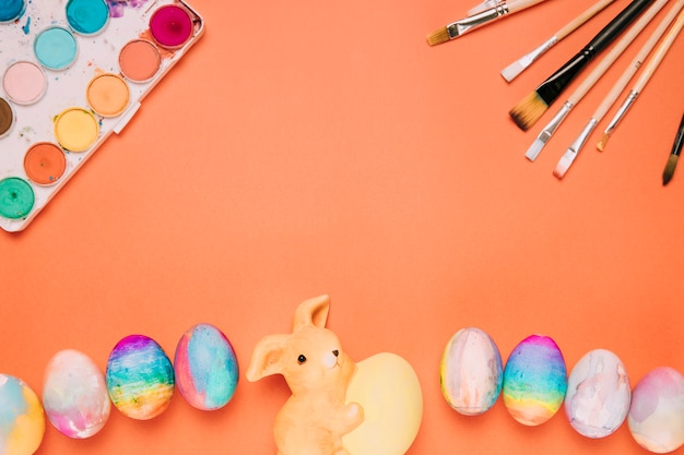 Huevos de pascua; pinceles; cuadro de pintura y estatua de conejo sobre un fondo naranja Foto gratis