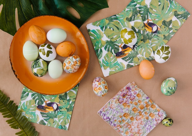 Huevos de pascua en un plato cerca de servilletas con pinturas tropicales y hojas Foto gratis