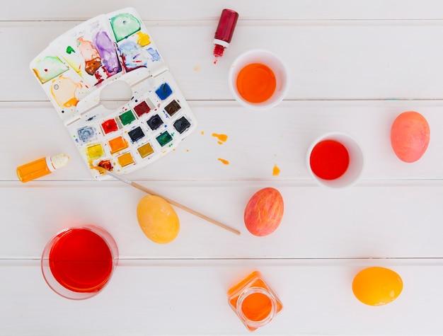 Huevos de pascua entre tazas con tinte líquido cerca de pincel con juego de colores Foto gratis