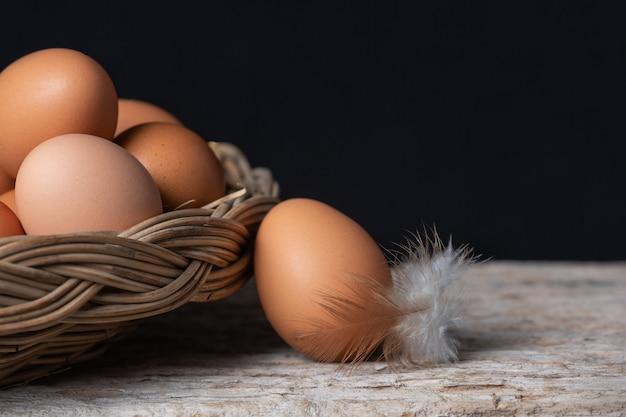 Huevos y plumas en una canasta Foto gratis
