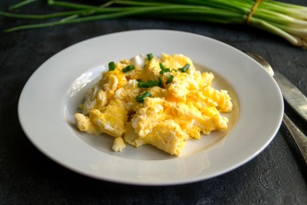 Huevos revueltos en un plato blanco. la vista desde la parte superior. Foto Premium