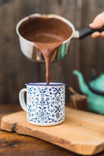 Humano con una cacerola que vierte líquido marrón en taza Foto gratis