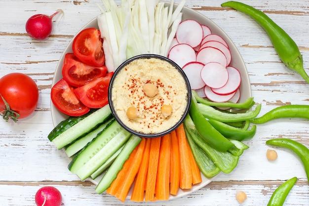 Hummus en un tazón, palitos de verduras, garbanzos, aceitunas. Foto Premium