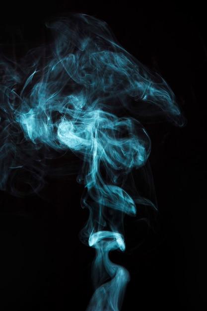 Humo azul claro sobre fondo negro Foto gratis