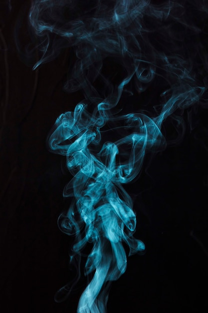 Humo azul sobre fondo negro con espacio de copia para escribir el texto Foto gratis