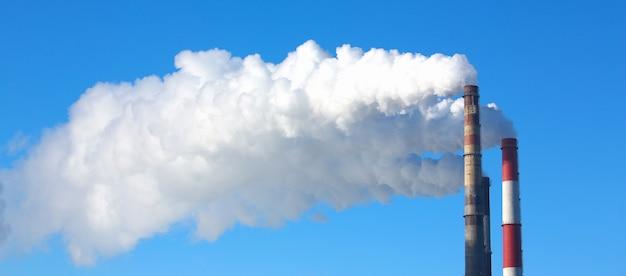 El humo blanco proviene de las tuberías contra el cielo azul. problema de emisiones nocivas y contaminación del aire de la población de calefacción central de las grandes ciudades concepto ecológico Foto Premium