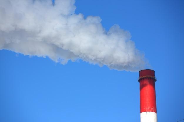 El humo blanco proviene de las tuberías contra el cielo azul Foto Premium