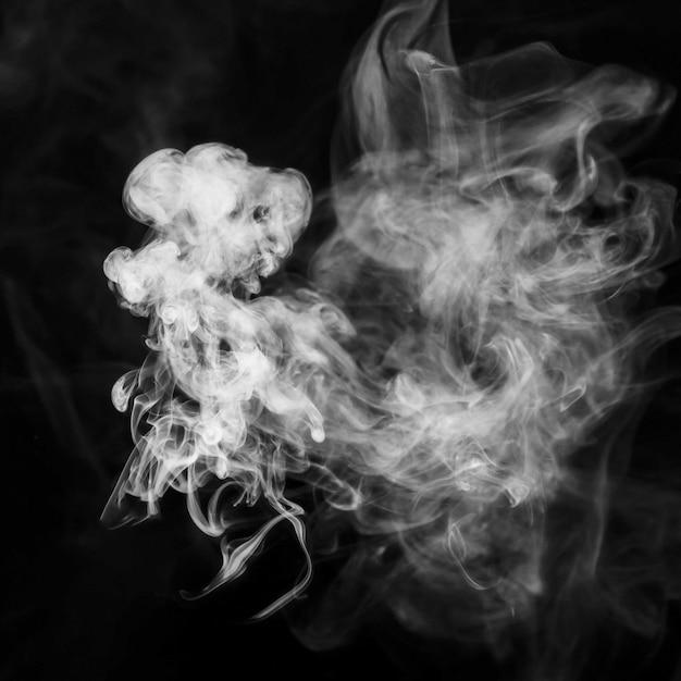 Humo blanco tenue transparente contra el fondo negro Foto gratis