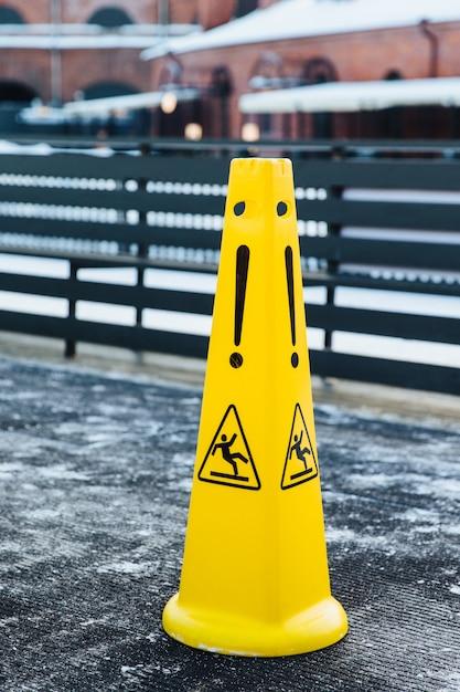 Icono resbaladizo en alertas de plástico amarillo sobre el peligro en la carretera. precaución señal de advertencia húmeda. Foto Premium