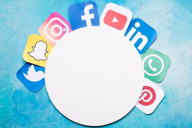 Iconos de aplicaciones de teléfonos móviles dispuestos alrededor de papel blanco circular Foto gratis