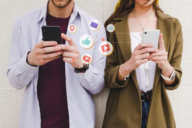 Iconos de notificación móvil entre hombre y mujer usando teléfono celular Foto gratis