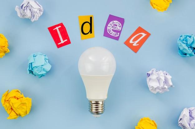 Idea colorida letras de palabras y bombilla real Foto gratis