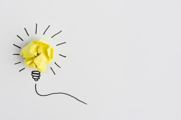 Idea creativa bombilla arrugada de papel amarillo sobre fondo blanco Foto gratis