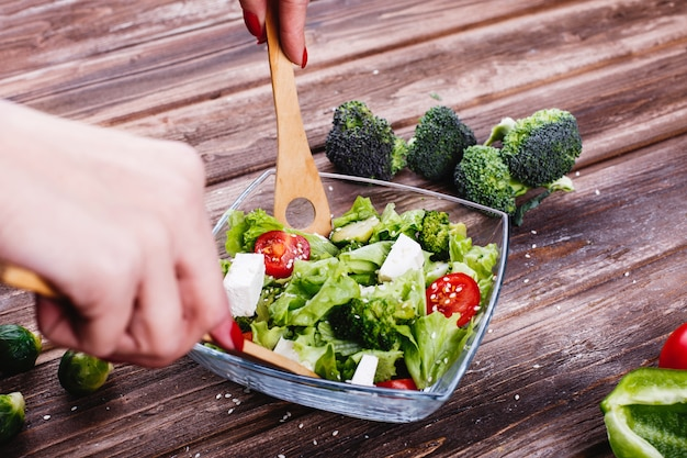 Ideas para el almuerzo o la cena. mujer agita ensalada fresca de verdor, aguacate, pimiento verde. Foto gratis