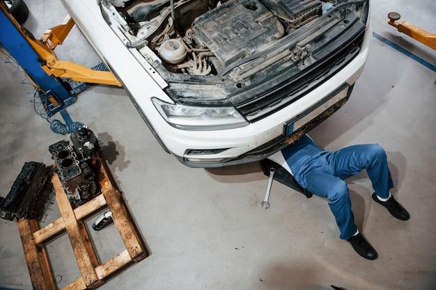 Iluminación artificial. empleado en el uniforme de color azul trabaja en el salón del automóvil Foto gratis