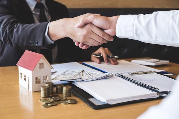 Imagen del acuerdo exitoso de bienes raíces, el corredor y el cliente se dan la mano después de firmar el formulario de solicitud aprobado del contrato, en relación con la oferta de préstamo hipotecario y el seguro de la casa Foto Premium