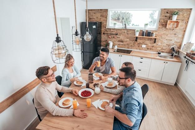 Imagen de alto ángulo de cinco amigos o compañeros de cuarto multiétnicos comiendo panqueques caseros. Foto Premium