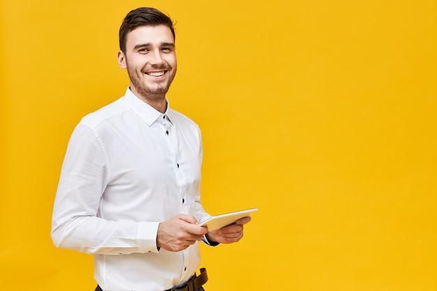 Imagen de un apuesto joven confiado en camisa blanca sosteniendo una tableta digital genérica y sonriendo ampliamente, disfrutando de los juegos usando la aplicación en línea. tecnología, entretenimiento y juegos Foto gratis