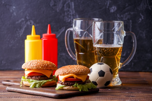 Imagen de dos hamburguesas, vasos, balón de fútbol, salsa de tomate Foto Premium