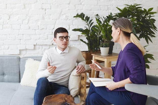 Imagen de frustrado joven caucásico vestido con suéter y anteojos sentado en un cómodo sofá, compartiendo sus problemas personales con una consejera de mediana edad durante la sesión de terapia Foto gratis