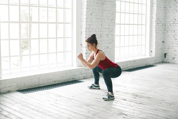 Imagen de fuerte chica deportiva vistiendo elegante camiseta sin mangas, zapatillas y leggings haciendo sentadillas sobre un piso de madera en el centro de gimnasio contra grandes ventanales Foto gratis