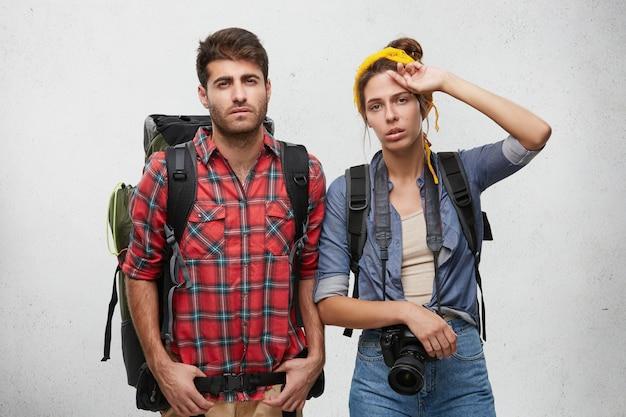 Imagen de un hombre y una mujer agotados y frustrados de aspecto europeo que llevan mochilas en los hombros sintiéndose cansados y agotados después de pasar una noche de insomnio en la carretera mientras hacía autostop Foto gratis