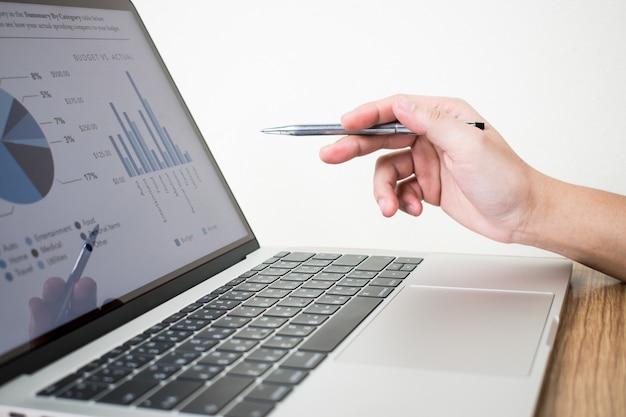 La imagen del hombre de negocios está analizando el gráfico en la computadora portátil. Foto Premium