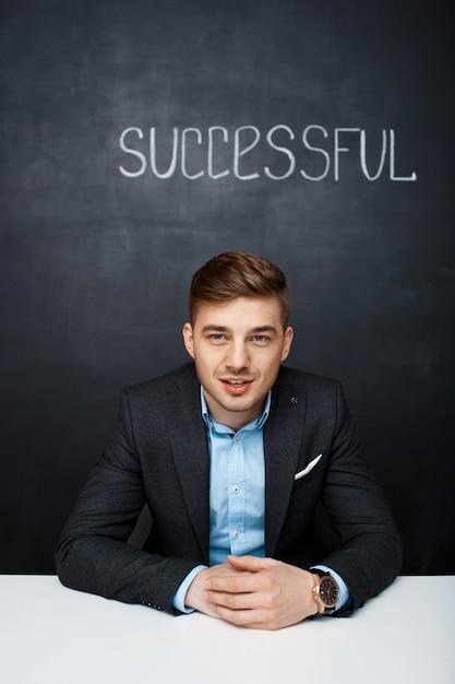 Imagen de un hombre que habla feliz sobre tablero negro con texto succ Foto gratis