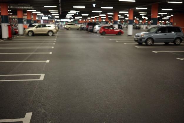 Imagen horizontal del interior del estacionamiento o garaje subterráneo con luces de neón y automóviles estacionados. edificios, construcciones urbanas, espacio, transporte, vehículo y concepto de ciudad nocturna Foto gratis